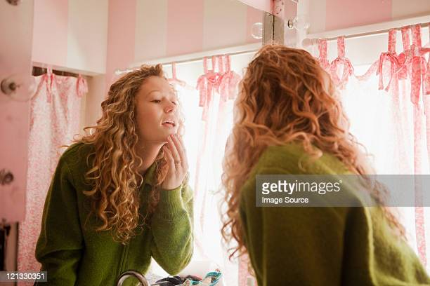 teenage girl checking skin in bathroom mirror - girl in mirror stock-fotos und bilder