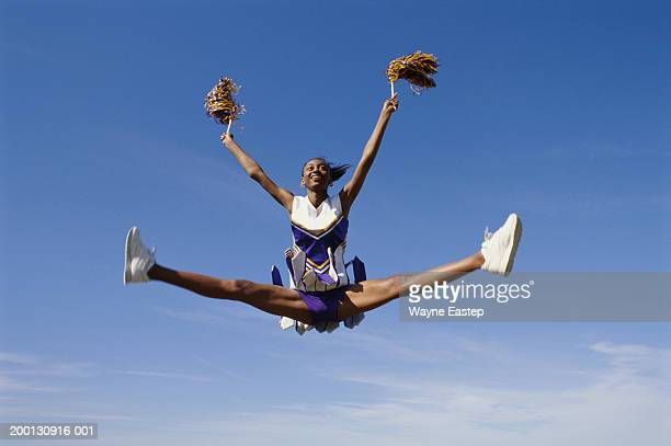 teenage girl cheerleader (16-18) leaping - cheerleader stock pictures, royalty-free photos & images