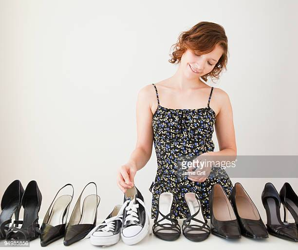 teenage girl choosing sneaker from row of heels - pump dress shoe stock pictures, royalty-free photos & images