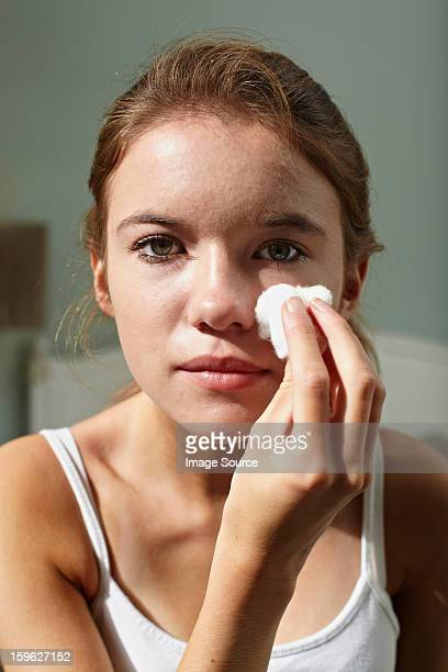 Teenage girl cleansing her face