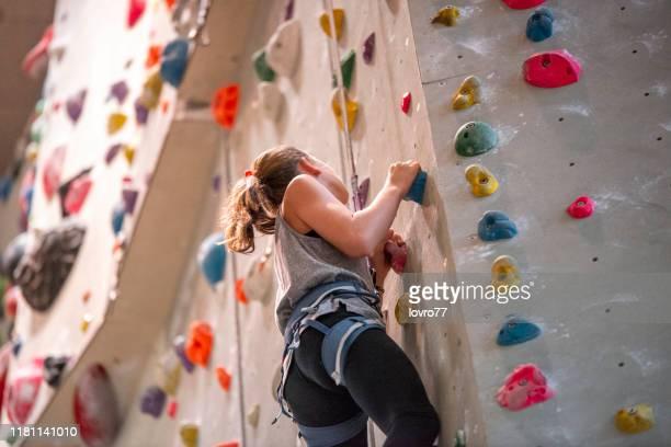 adolescente che si arrampica sulla parete da arrampicata - scalare foto e immagini stock