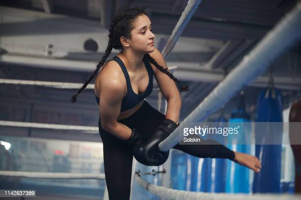 teenage girl climbing over boxing ring ropes - women's boxing stock pictures, royalty-free photos & images
