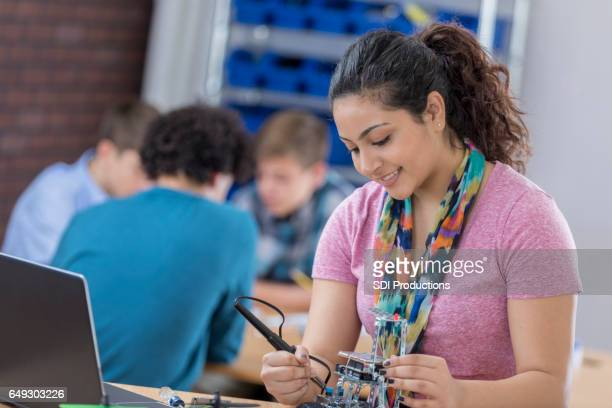 Teenage girl concentrates on robotics project at school