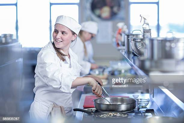 Teenage girl cooking in canteen kitchen