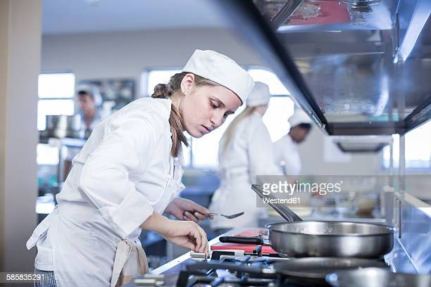 teenage girl cooking in canteen kitchen - teenagers only stock pictures, royalty-free photos & images