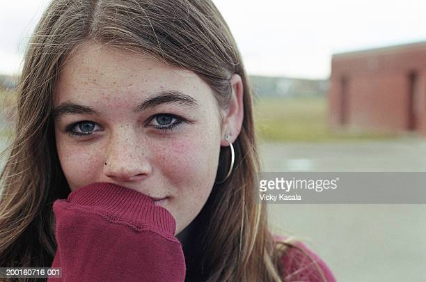 teenage girl (13-15) covering mouth with sweatshirt sleeve - verlegen stockfoto's en -beelden