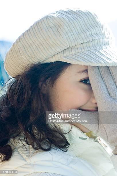 Teenage girl covering part of face with gloved hand, close-up