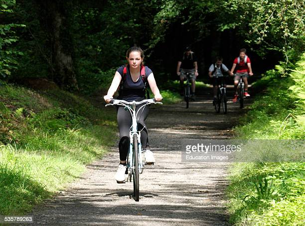 Teenage girl cycling along the Camel Trail near Bodmin followed by her family Cornwall UK