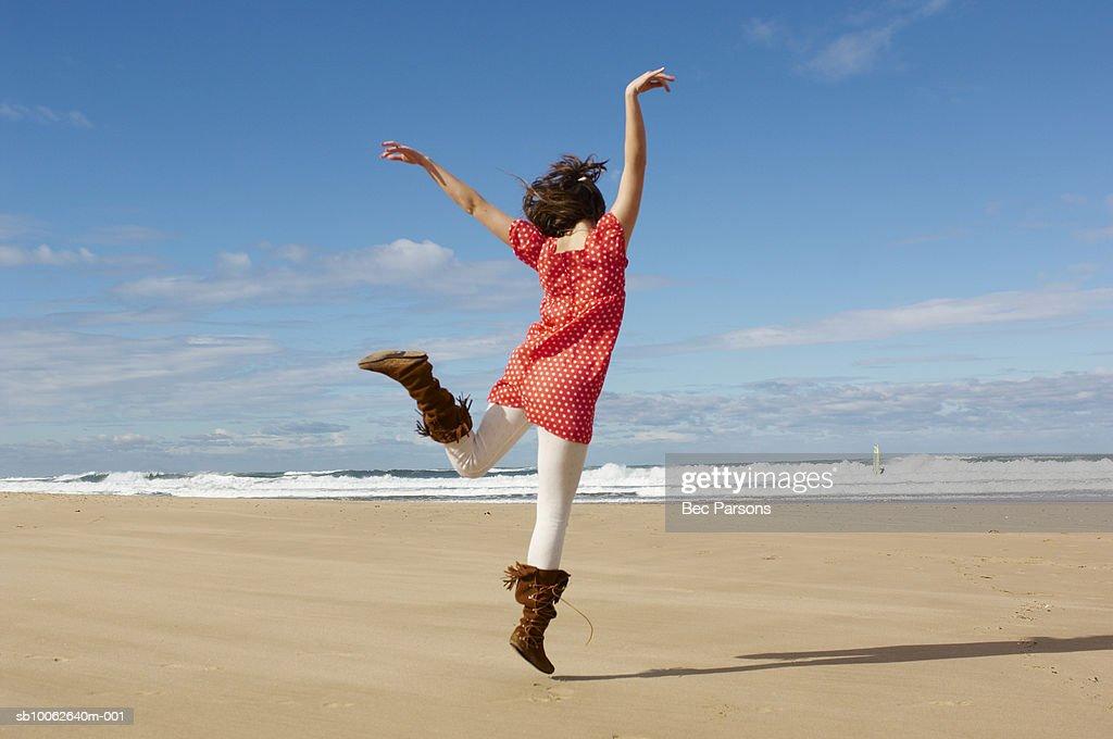 Teenage girl (16-17) dancing on beach, rear view : Stock Photo