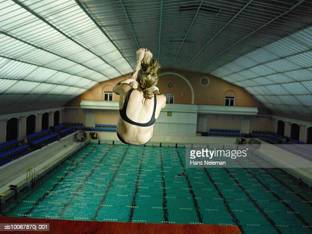 teenage girl (14-15) diving in swimming pool, rear view - 室内プール ストックフォトと画像