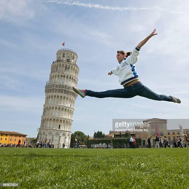 Teenage girl does jump split beside Tower of Pisa
