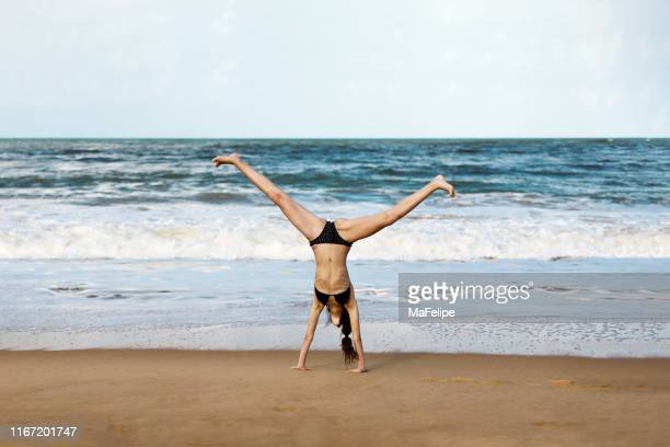 teenage girl doing a cartwheel at the beach - one teenage girl only stock pictures, royalty-free photos & images