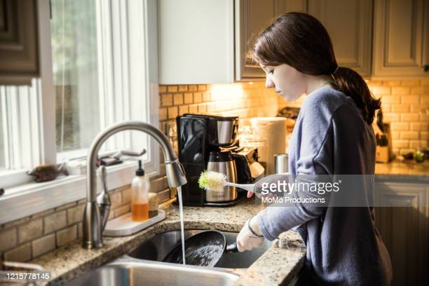 teenage girl doing dishes in kitchen - chores stock pictures, royalty-free photos & images