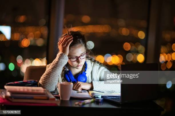 teenage girl doing homework at night - toughness stock pictures, royalty-free photos & images