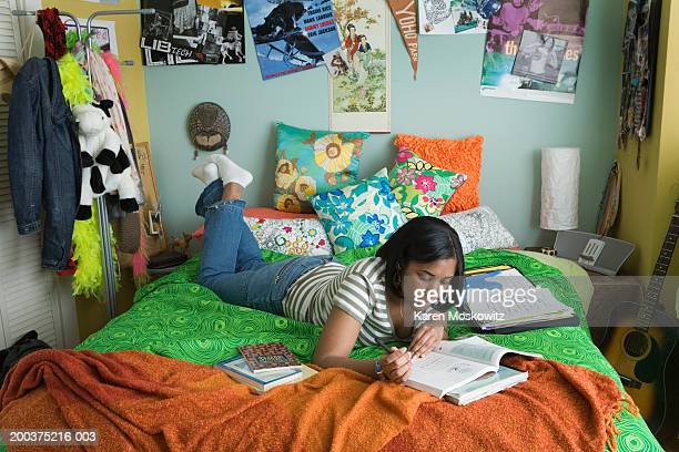 Teenage girl (15-17) doing homework on bed, wearing headphones