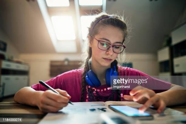 teenager-mädchen macht hausaufgaben - abgelenkt stock-fotos und bilder