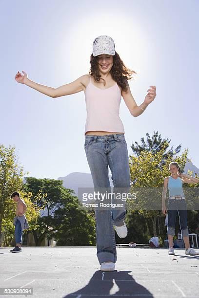 Teenage Girl Doing Hopscotch
