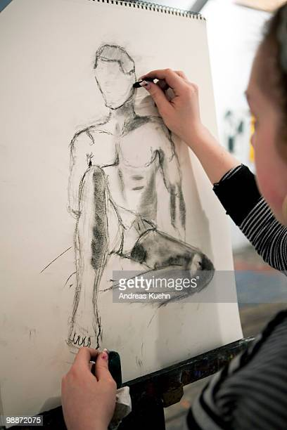 Teenage girl drawing a picture of nude man.