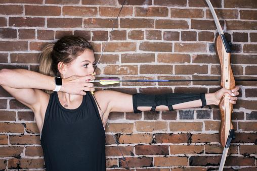 Teenage girl drawing her bow at indoor archery range - gettyimageskorea