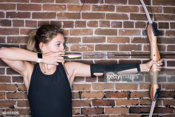 Teenage girl drawing her bow at indoor archery range