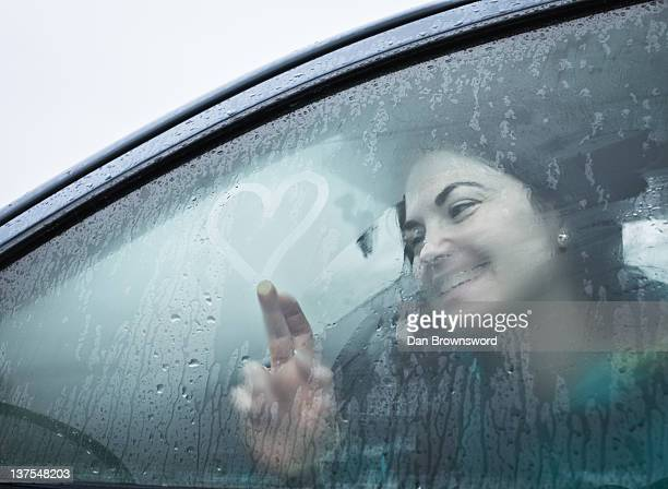 Teenage girl drawing on wet car window