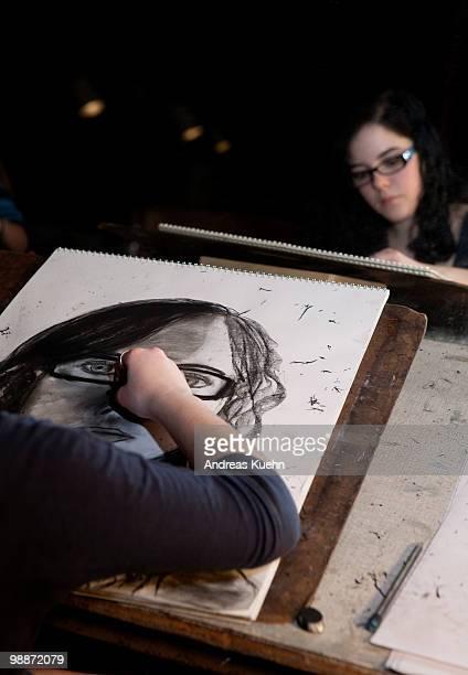 Teenage girl drawing self portrait.