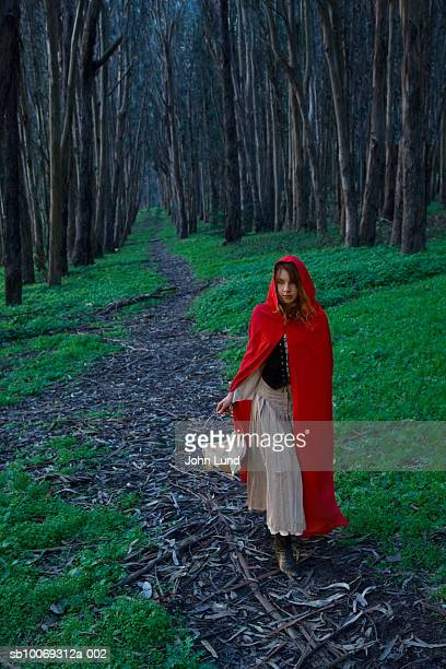 Teenage Girl (14-15) dressed as little red riding hood in forest