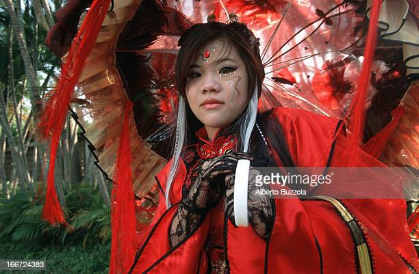 A teenage girl dressed in a red costume of a modern Japanese comic character poses at a 'Cosplay' 'Cosplay' or 'Costume Play' is a Japanese...