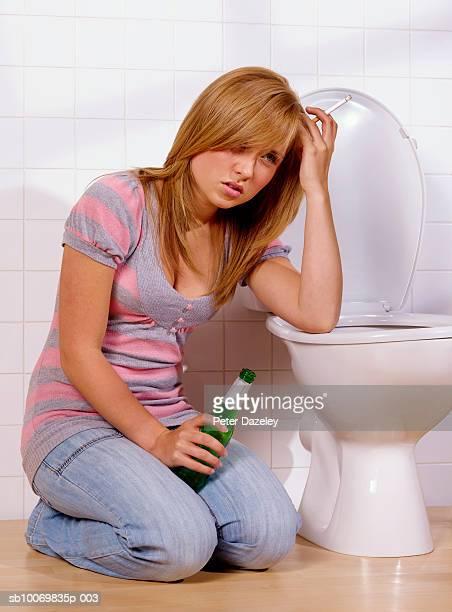 Teenage girl (16-17) drinking and smoking in toilet