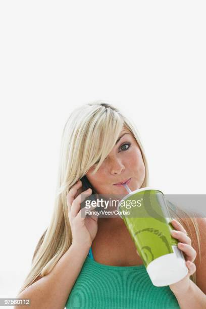 Teenage girl drinking and talking on cell phone