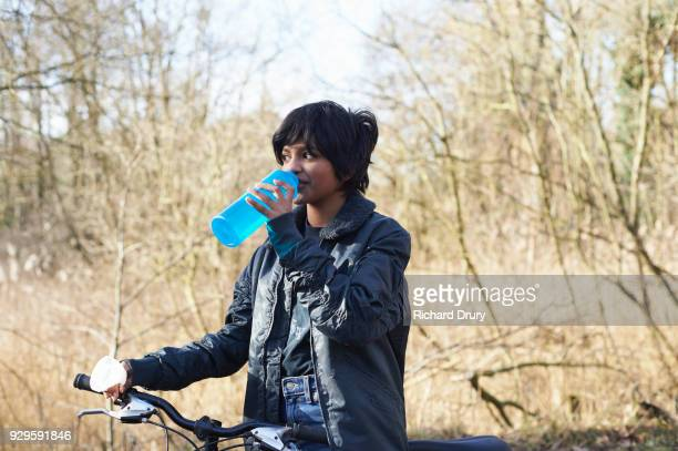 Teenage girl drinking from water bottle on cycle ride