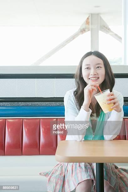 teenage girl drinking juice - alleen tieners stockfoto's en -beelden