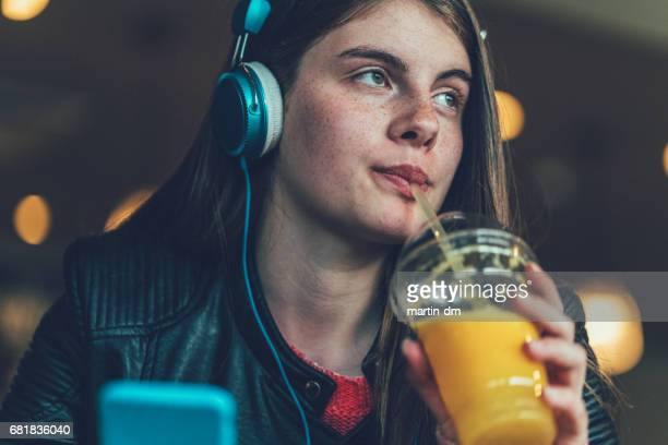teenage girl drinking orange juice - mp3 juices stock photos and pictures