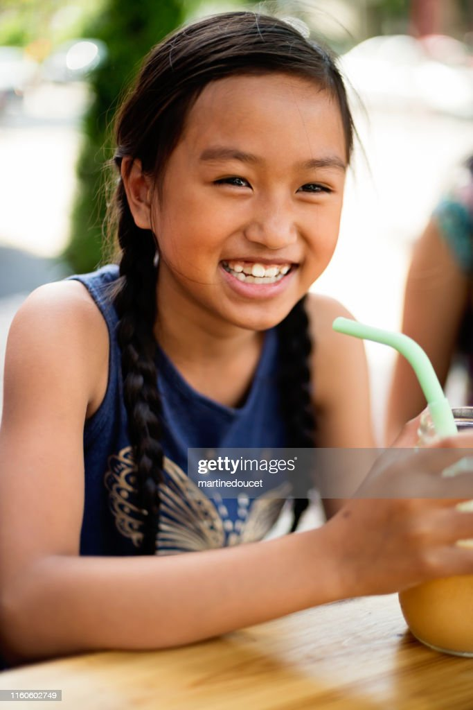 Teenage girl drinking smoothie in reusable jar with reusable straw. : Stock Photo