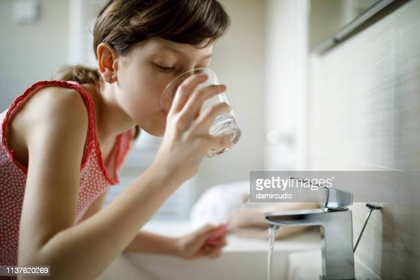 teenage girl drinking water while holding toothbrush in bathroom - mouthwash stock pictures, royalty-free photos & images