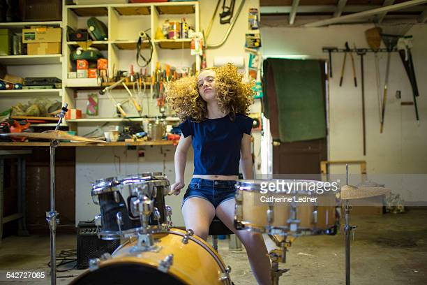 Teenage girl drumming in garage.