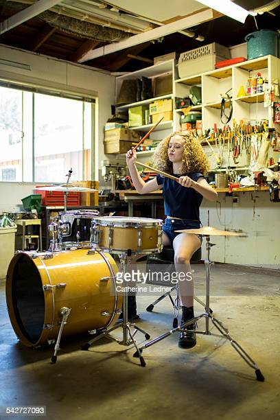 Teenage girl drumming in garage