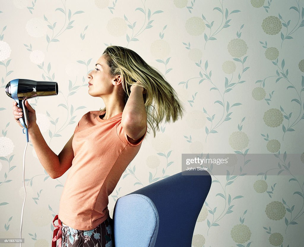 Teenage Girl Drying Her Hair With a Hairdryer : Stock Photo