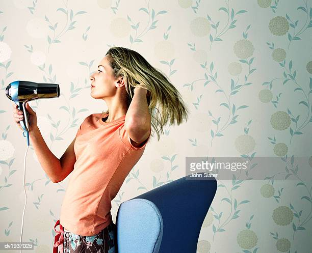 Teenage Girl Drying Her Hair With a Hairdryer