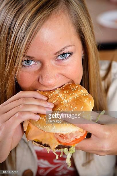 Teenage Girl Eating a Cheeseburger