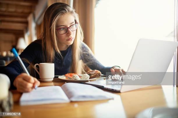 mädchen essen frühstück und hausaufgaben - hausaufgabe stock-fotos und bilder