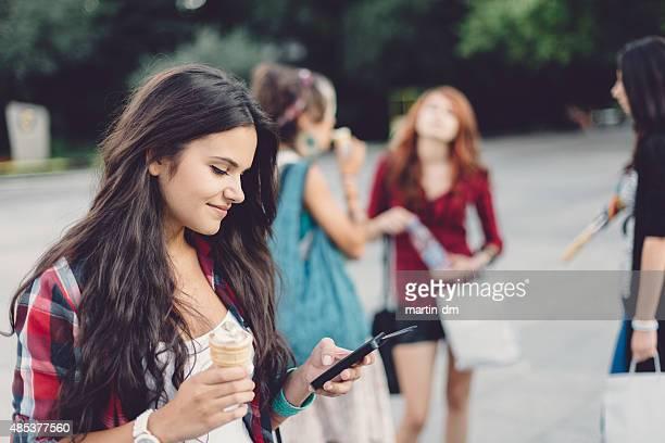 Teenage girl eating Eis und SMS auf Handy