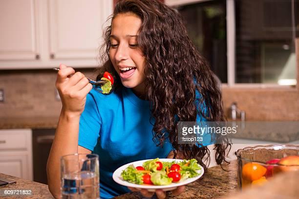 Teenage girl eating salad for dinner after school.