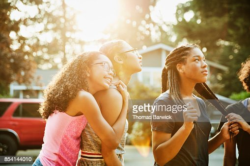 Teenage girl embracing friend while hanging out in neighborhood on summer evening