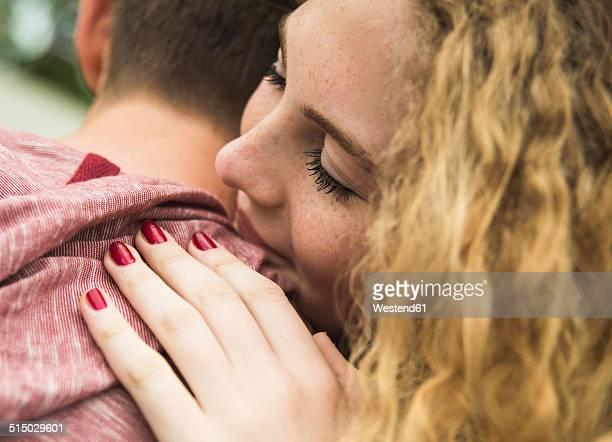 Teenage girl embracing her boyfriend, partial view
