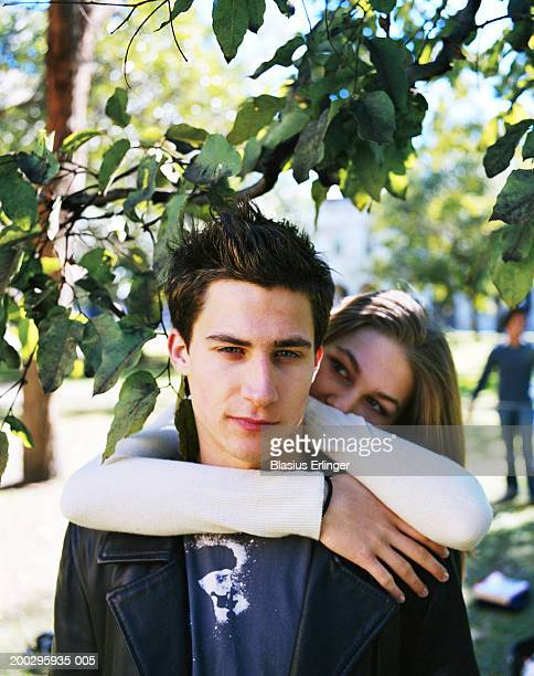 teenage girl (16-18) embracing teenage boy (17-19) on campus - blasius erlinger stock pictures, royalty-free photos & images