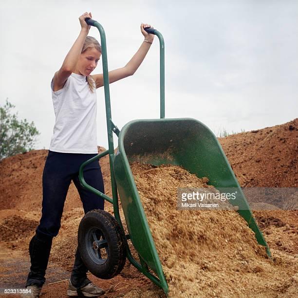 Teenage Girl Emptying Wheelbarrow