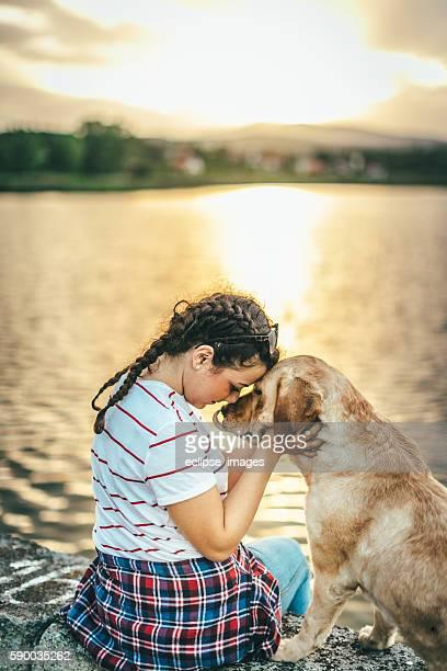 Teenage girl enjoying golden sunset with her dog
