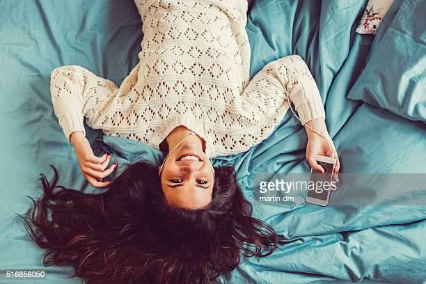 Teenage girl enjoying the music in bed