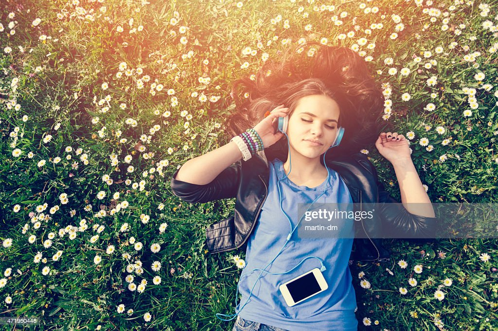 Teenage girl enjoying the music in the park : Stock Photo